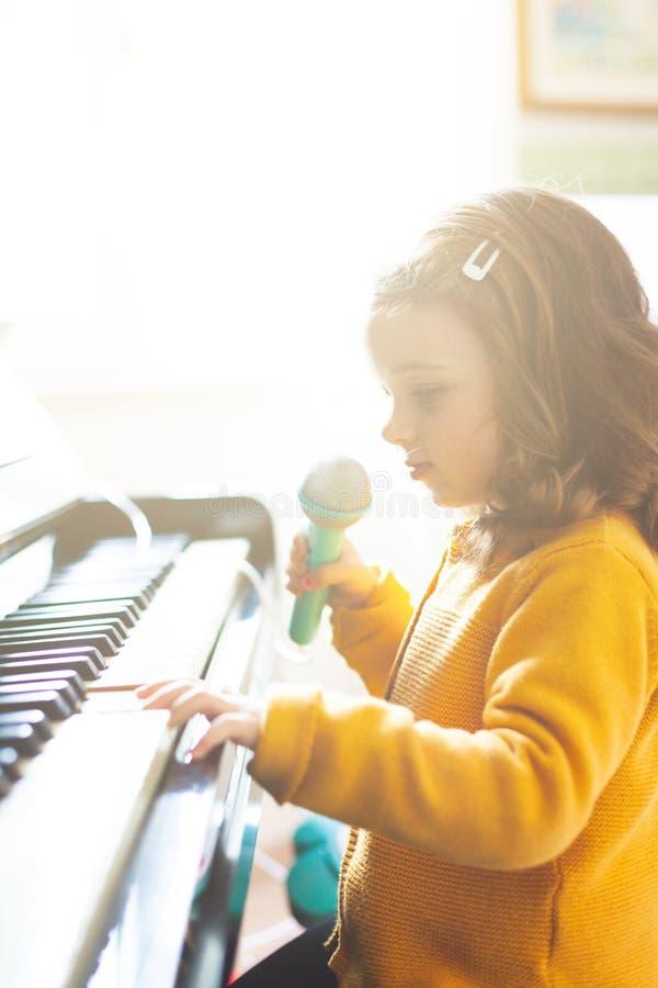 女孩小孩使用与钢琴和玩具话筒 免版税库存图片