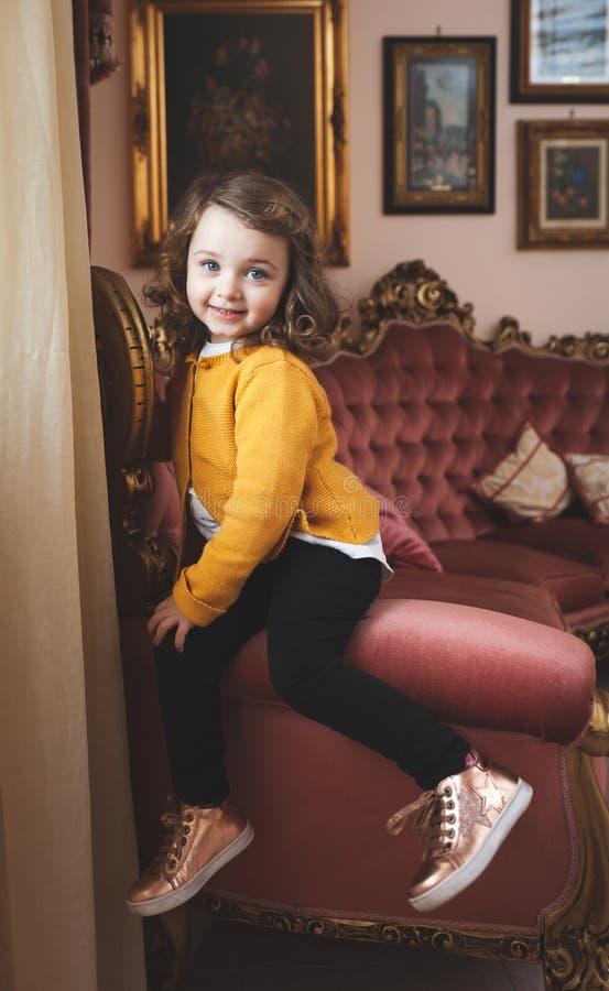 女孩小孩在有巴洛克式的装饰的一个客厅 免版税库存图片