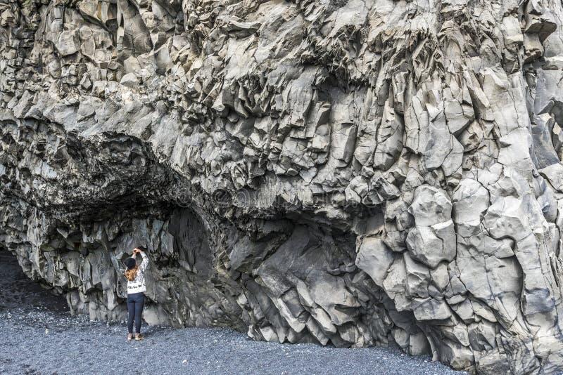 女孩少年在Reynisfjall山底部拍玄武岩峭壁的照片在冰岛南部 图库摄影