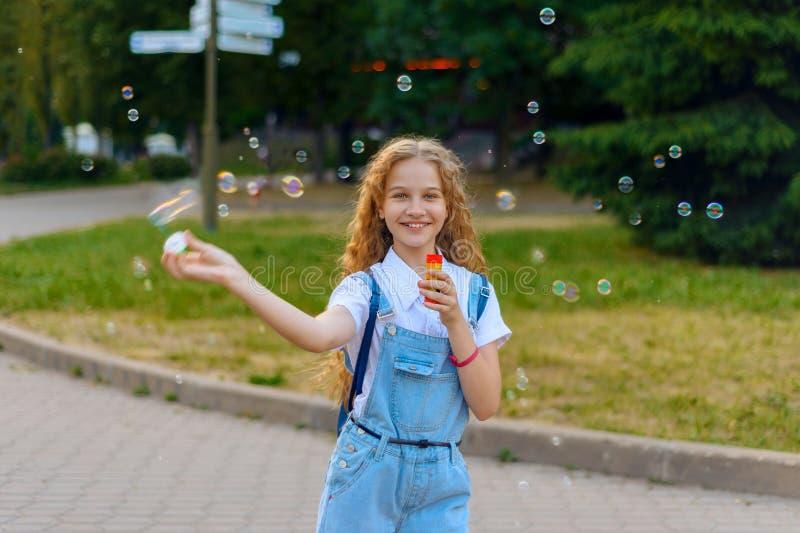 女孩少年愉快的微笑的打击肥皂泡 免版税库存图片