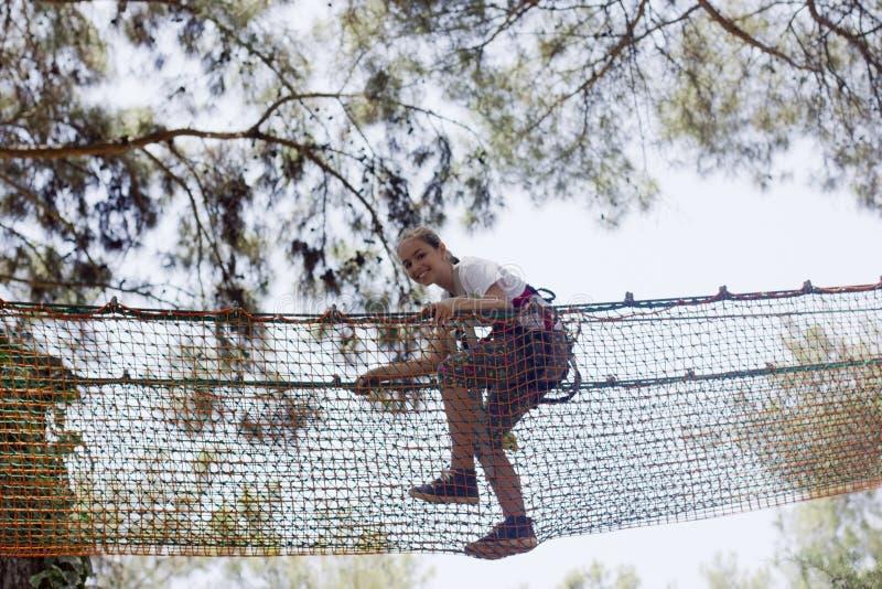 女孩少年用上升的设备在绳索游乐园 库存图片
