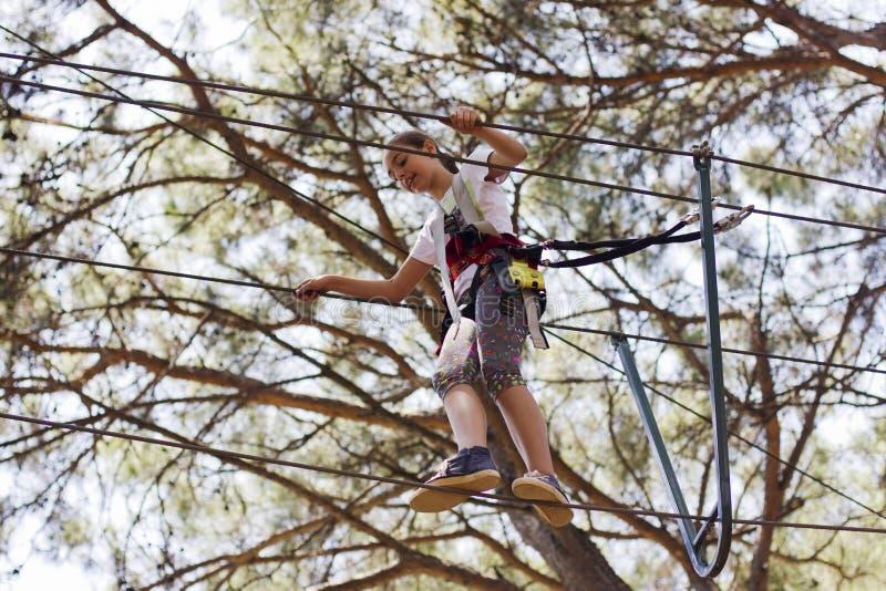 女孩少年用上升的设备在绳索游乐园 免版税库存图片