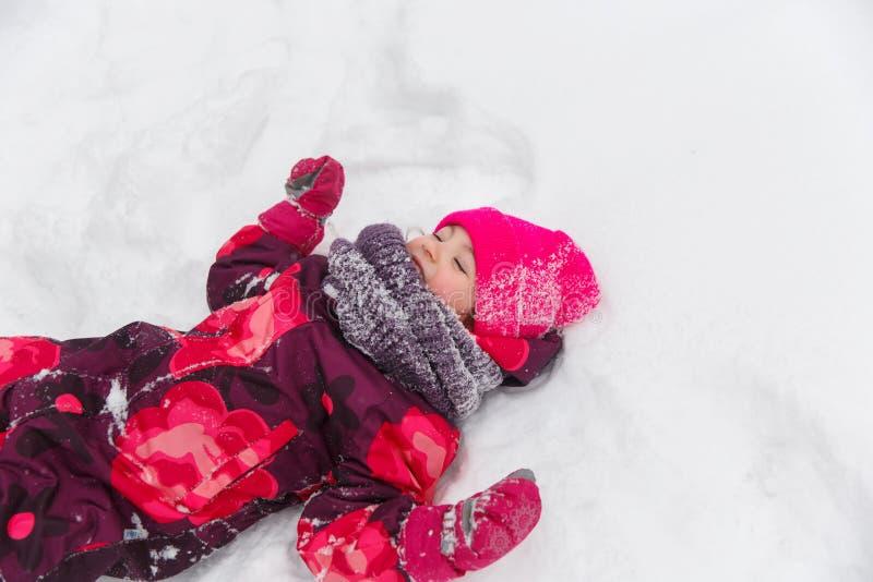 女孩少许位于的雪 免版税库存图片