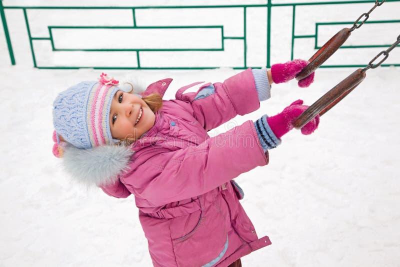 女孩少许操场微笑的冬天 免版税库存图片