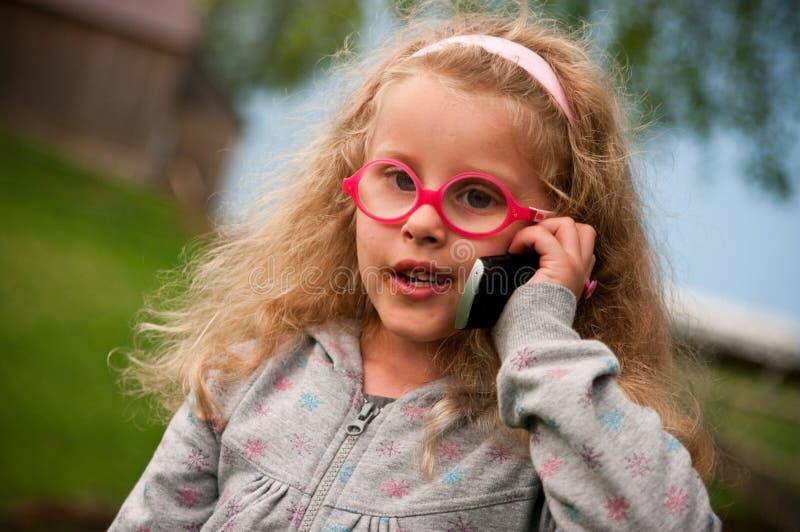 女孩少许移动电话 图库摄影