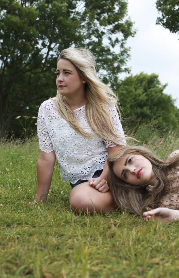 在与她的头的草一的两个十几岁的女孩在另一个女孩膝盖 照片拍摄时间