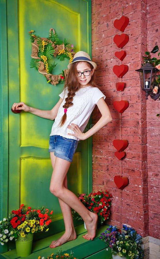 女孩少年在乡间别墅门廊站立  库存照片