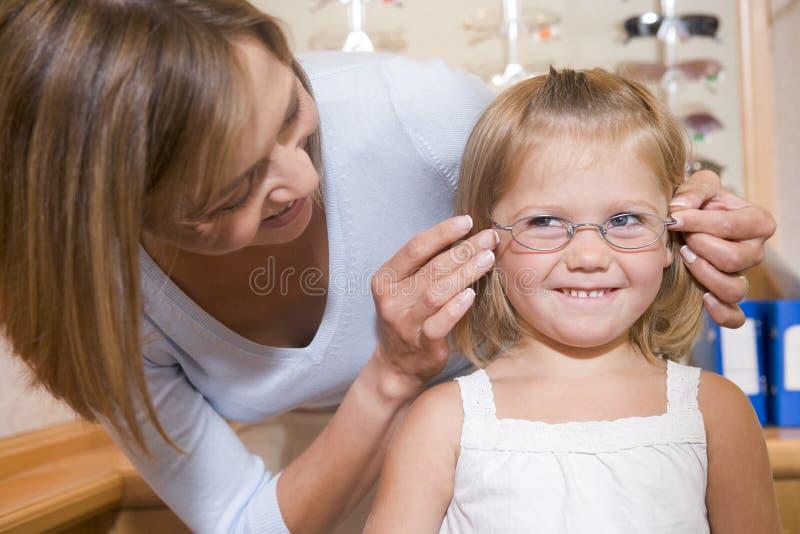 女孩尝试妇女年轻人的玻璃验光师 免版税库存图片