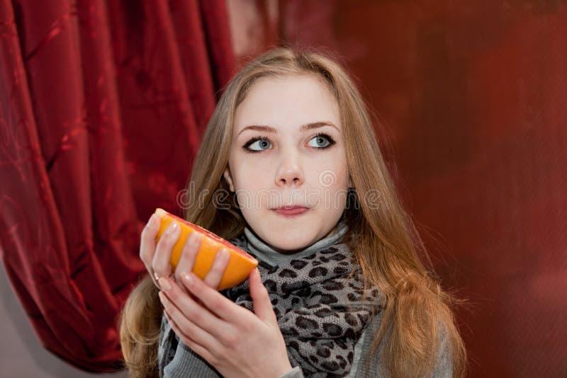 女孩尝试对一半在伯根地背景的一个葡萄柚 免版税库存照片