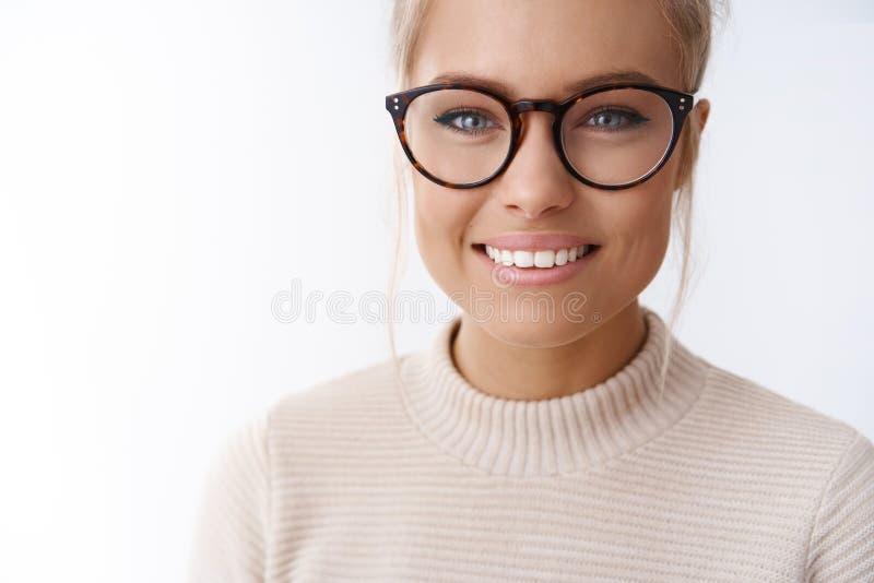 女孩崇拜新的玻璃采摘在站立眼镜师的商店愉快和高兴反对白色背景微笑满意 免版税图库摄影