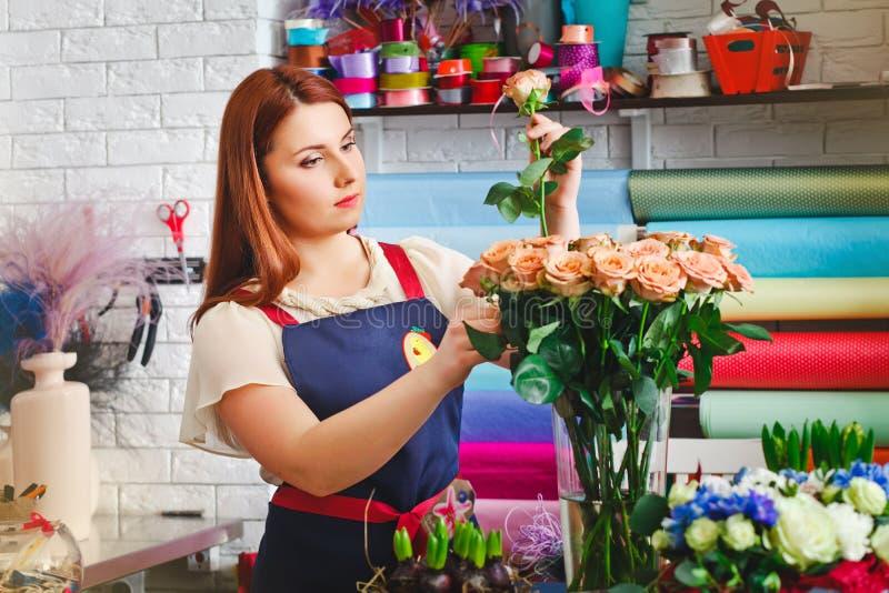 女孩工作在花店的,卖花人妇女做花束 免版税图库摄影