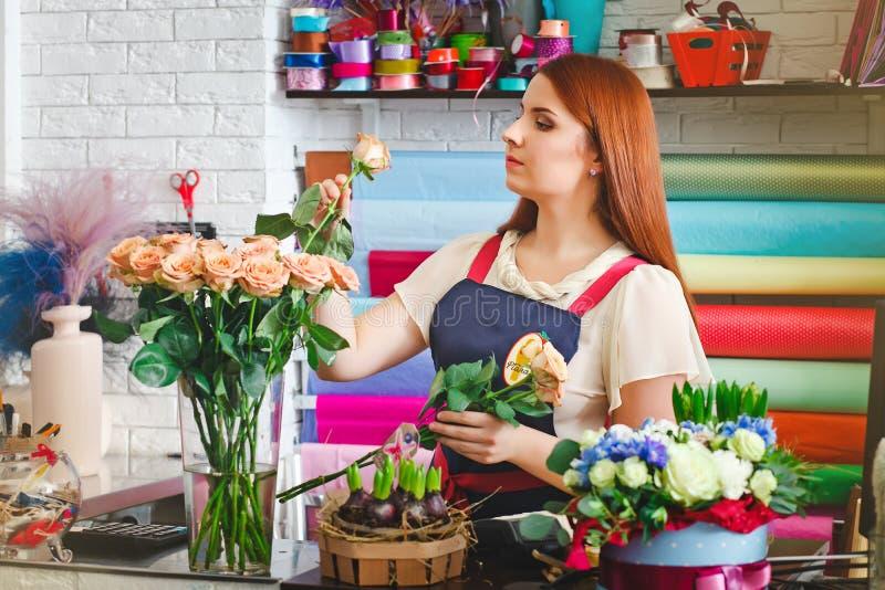 女孩工作在花店的,卖花人妇女做花束 图库摄影