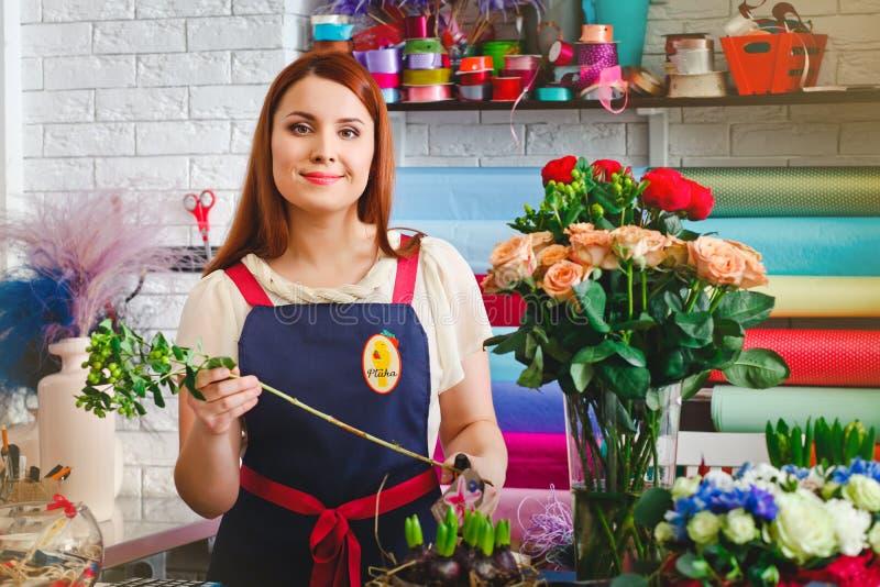 女孩工作在花店的,卖花人妇女做花束 库存图片