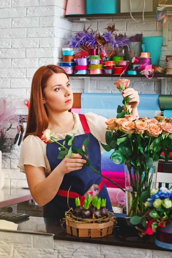 女孩工作在花店的,卖花人妇女做花束 免版税库存图片