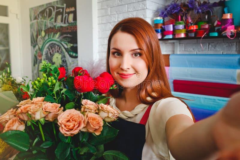 女孩工作在花店的,卖花人妇女做花束 库存照片