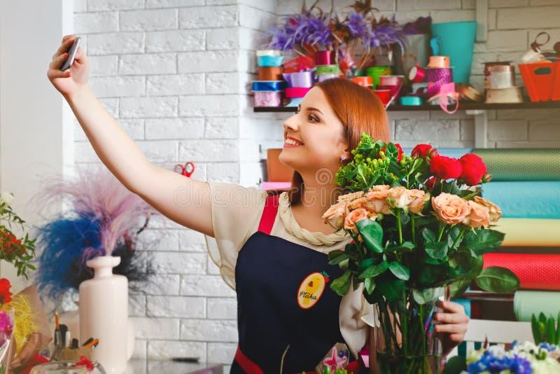 女孩工作在花店的, Floristry做与花花束的selfie照片  免版税库存照片