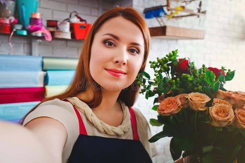 女孩工作在花店的, Floristry做与花花束的selfie照片  免版税图库摄影