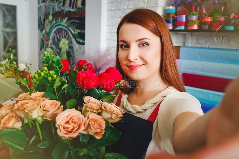 女孩工作在花店的, Floristry做与花花束的selfie照片  库存图片