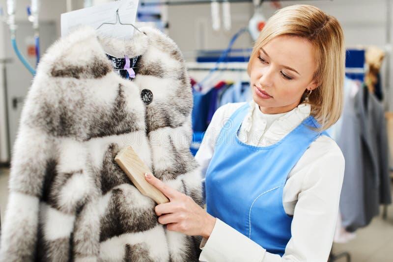 女孩工作者执行干燥洗衣店,手清洁毛皮服装 库存图片