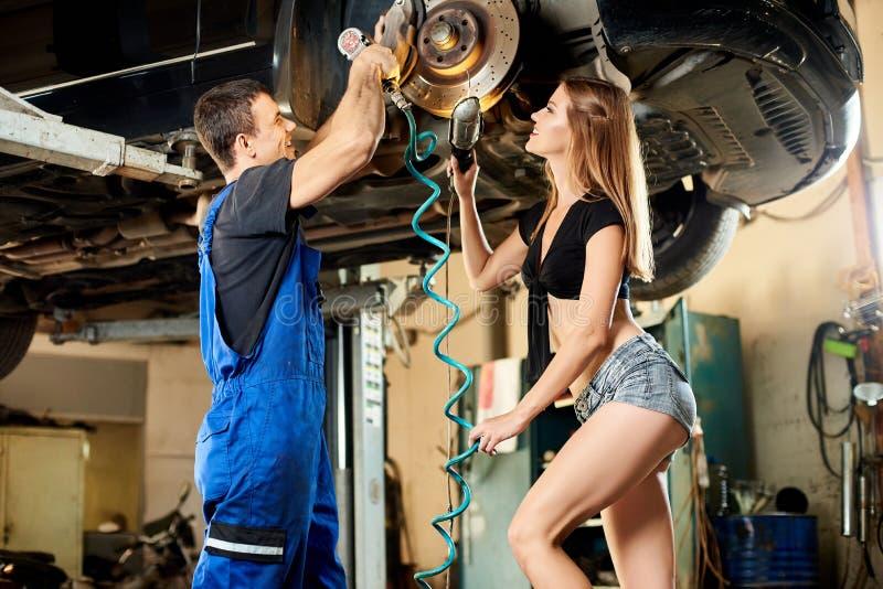 女孩帮助一位技工修理汽车操纵机构  免版税库存照片