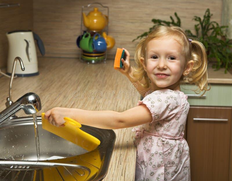女孩帮助厨房一点 图库摄影