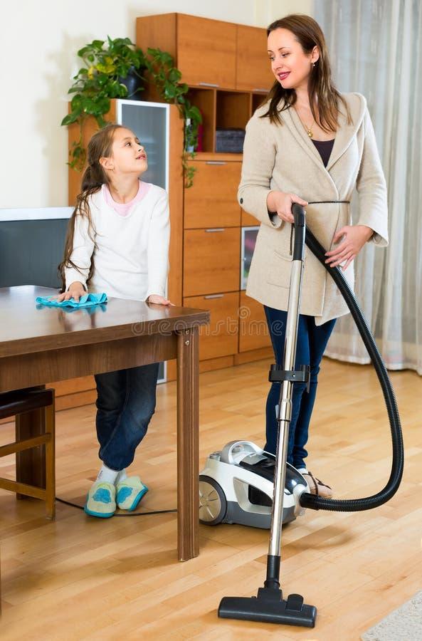 女孩帮助母亲到洁净室 免版税库存图片