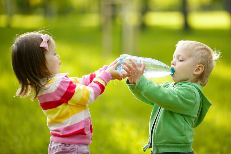 女孩帮助男孩保留瓶 免版税图库摄影