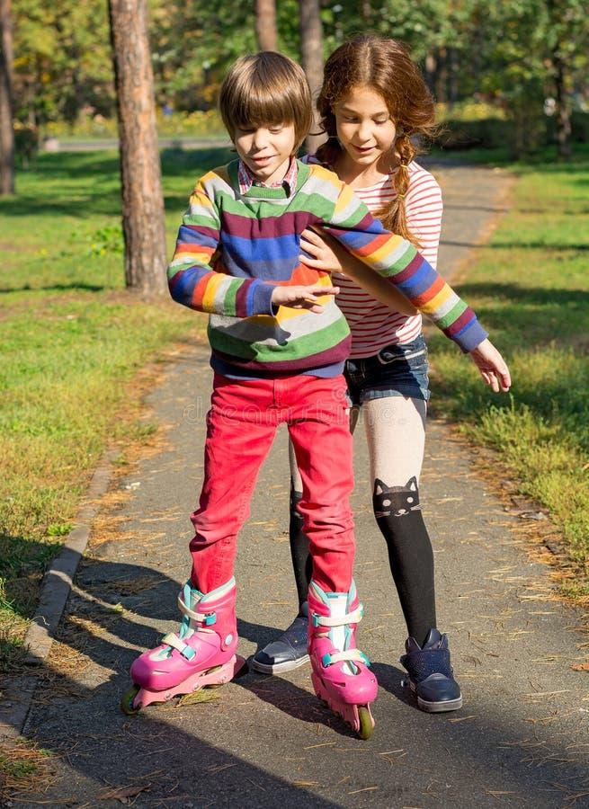 女孩帮助男孩路辗冰鞋 免版税库存照片