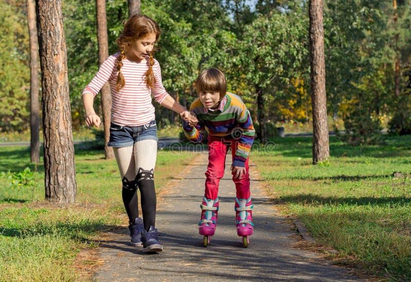 女孩帮助男孩路辗冰鞋 库存照片