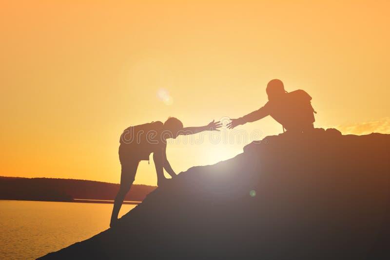 女孩帮助的人配合成功剪影在顶面山的 免版税库存照片