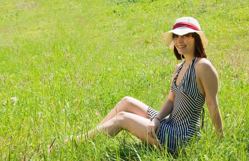 女孩帽子位于的草甸 免版税库存照片