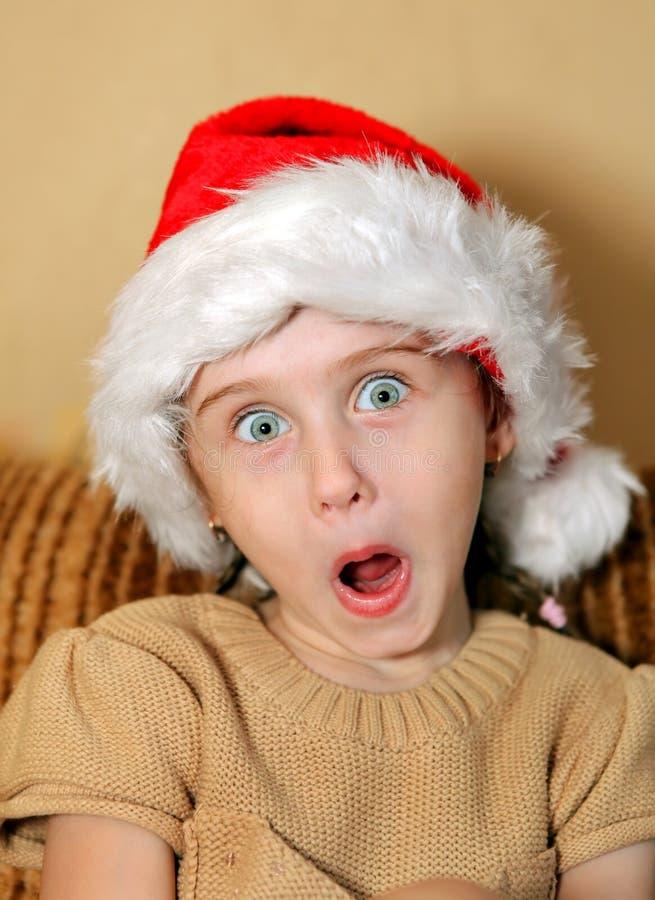 女孩帽子圣诞老人惊奇了 免版税库存照片