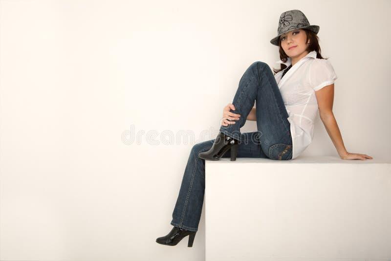 女孩帽子牛仔裤衬衣坐的白色 库存照片