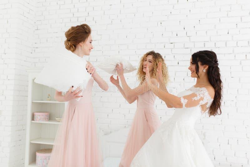 女孩庆祝新娘一个bachelorette党  与在白色砖墙背景的女傧相枕头战斗 免版税图库摄影