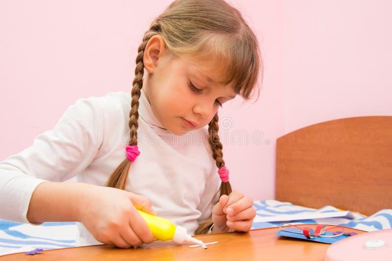 女孩应用胶浆于工艺在色纸外面 免版税库存图片