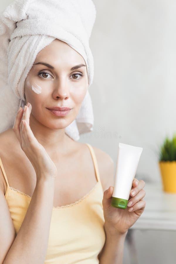 女孩应用面霜 护肤和秀丽概念 应用在她的面孔的少妇润肤霜 面孔护肤 免版税库存图片