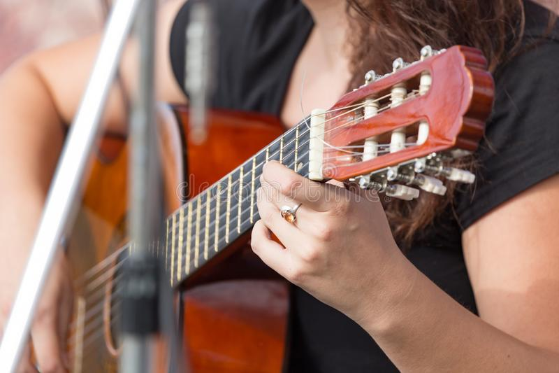女孩弹吉他的` s手 免版税库存照片