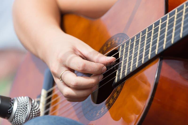 女孩弹吉他的` s手 免版税图库摄影