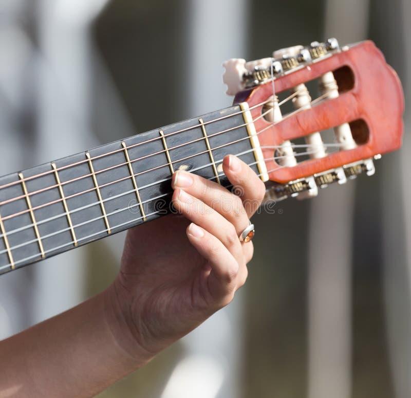 女孩弹吉他的` s手 库存照片