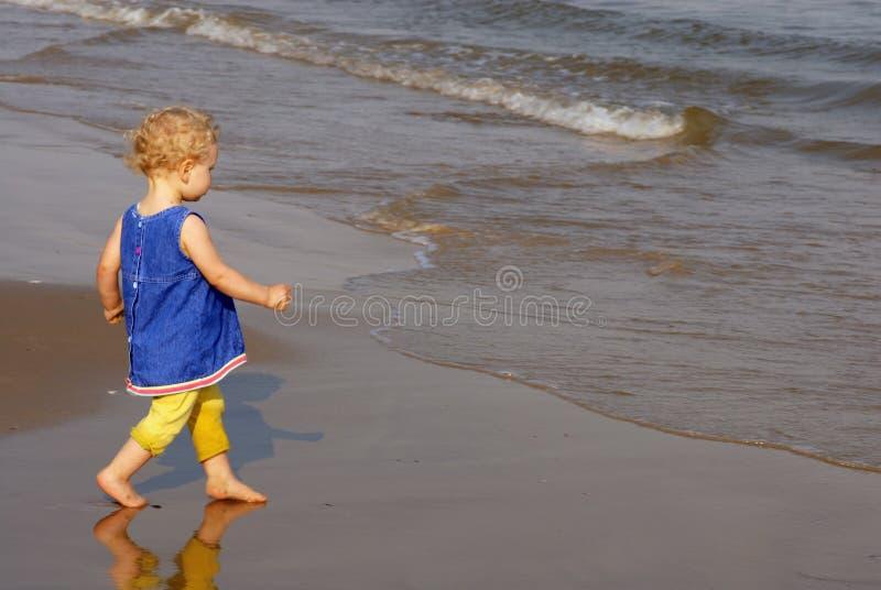 女孩往走的少许海滨 免版税库存图片