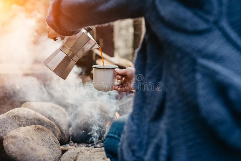 女孩徒步旅行者倒本身热的咖啡近对在时间日落的篝火 女性坐和拿着一个杯子在远足以后的咖啡 免版税图库摄影