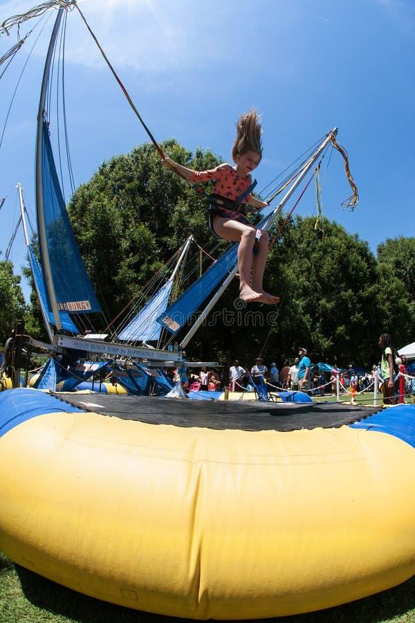 女孩得到空中弹起在橡皮筋绷床在亚特兰大节日 免版税库存图片