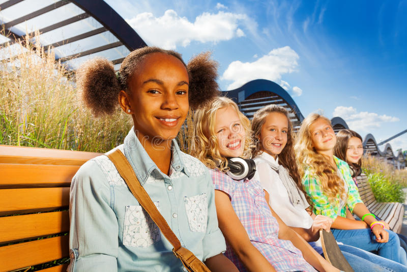女孩微笑和坐长凳在夏天 库存照片