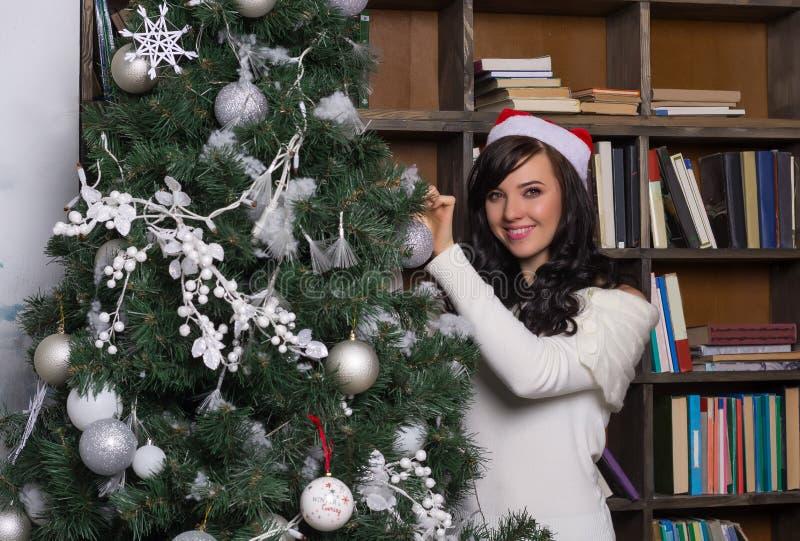 女孩微笑在嘘附近装饰圣诞树在屋子里 库存照片
