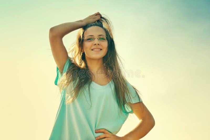 女孩微笑快乐,友好和迷住看照相机在温暖的晴朗的夏日 免版税库存照片