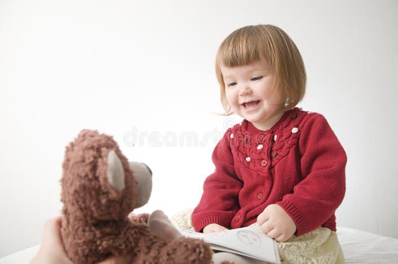 女孩微笑愉快 有熊的逗人喜爱的白种人在白色背景隔绝的婴孩和玩偶 免版税库存照片