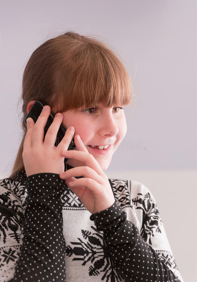 女孩微笑的谈话电话 免版税库存照片