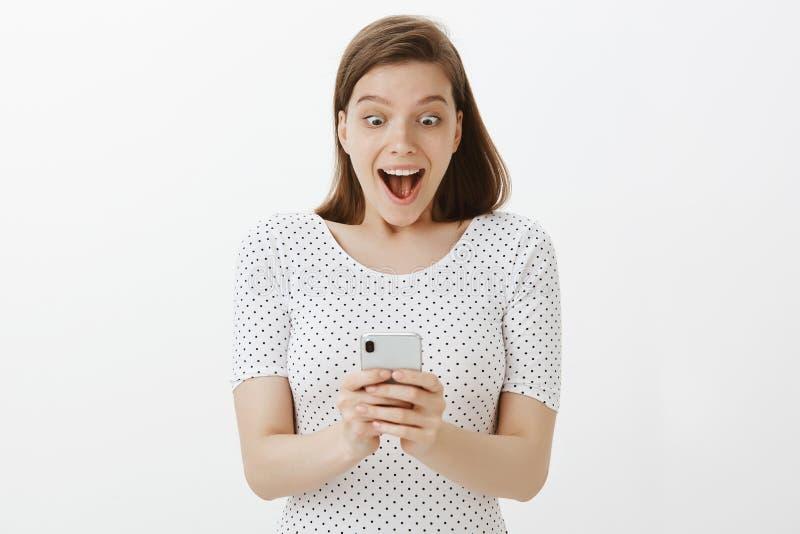 女孩怎么收到了在银行账户的金钱,激动和喜欢,认为花费他们,喘气和投下下颌与 免版税库存图片
