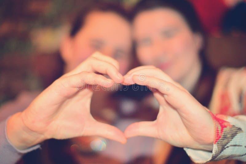 女孩急拉心脏用他们的手 爱和喜悦的概念 免版税图库摄影