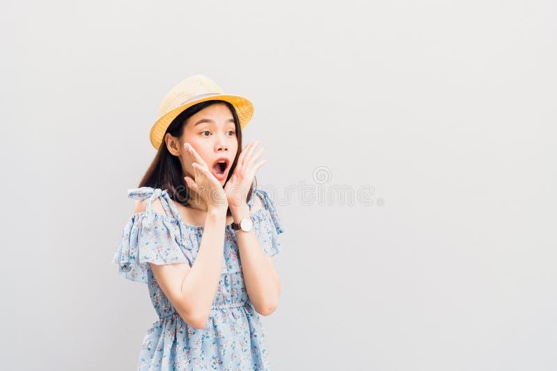 女孩愉快微笑和快乐在下巴的蓝色礼服和推力手上 概念夏天旅行 免版税库存照片